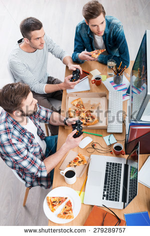 stock-photo-relaxing-after-work-top-view-of-three-young-men-playing-computer-games-and-eating-pizza-while-279289757